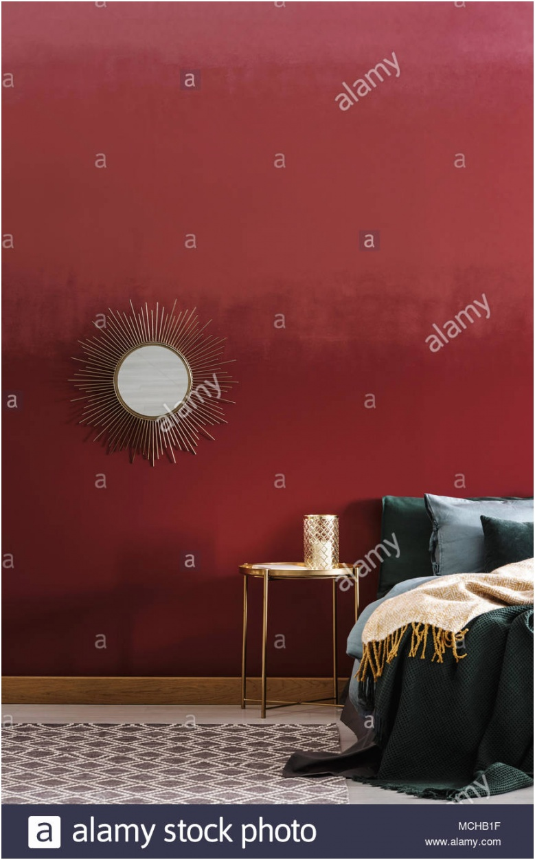 golden decorative round mirror hanging on a burgundy wall in bedroom interior MCHB1F