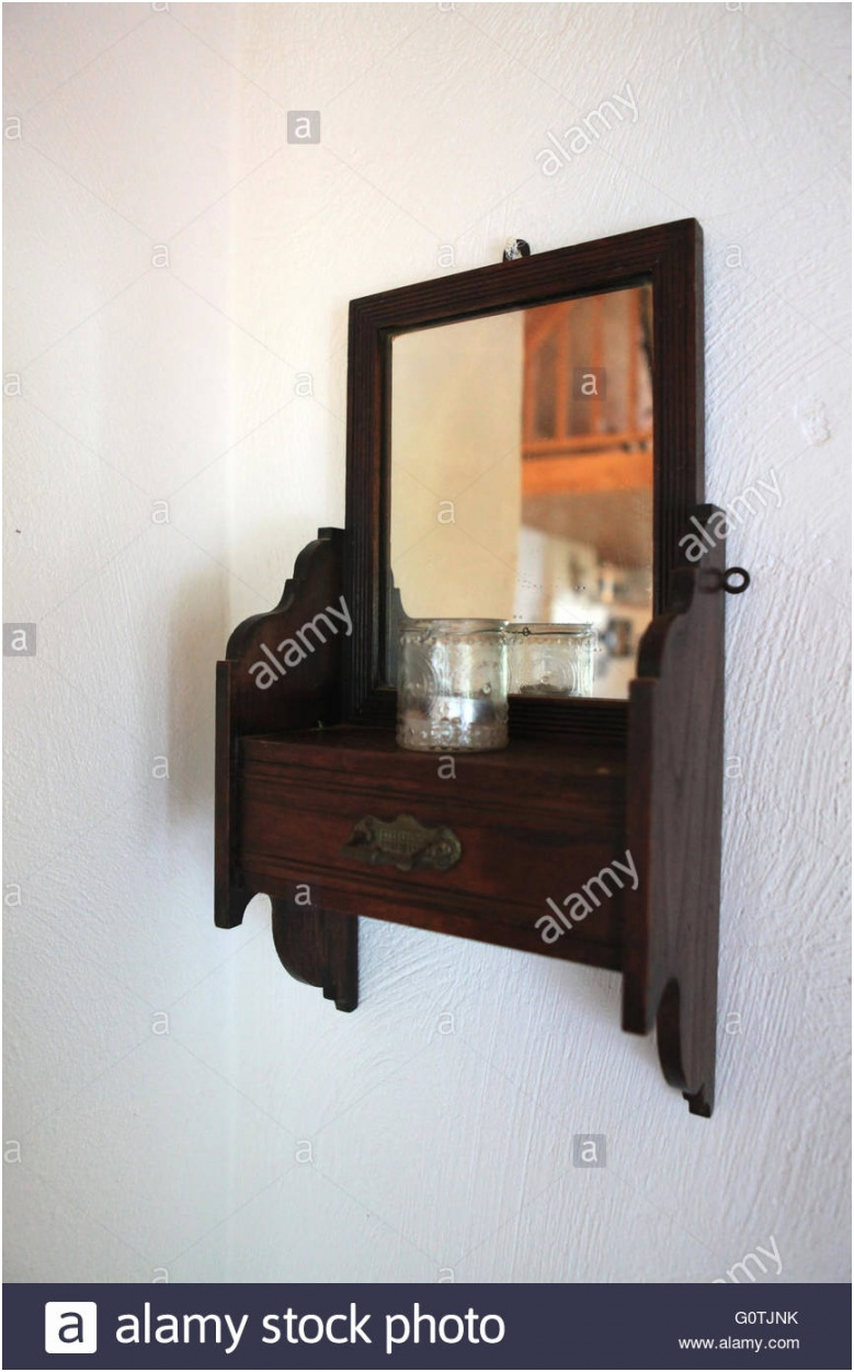 old vintage antique wooden mirror on a wall in a bedroom in a cottage G0TJNK