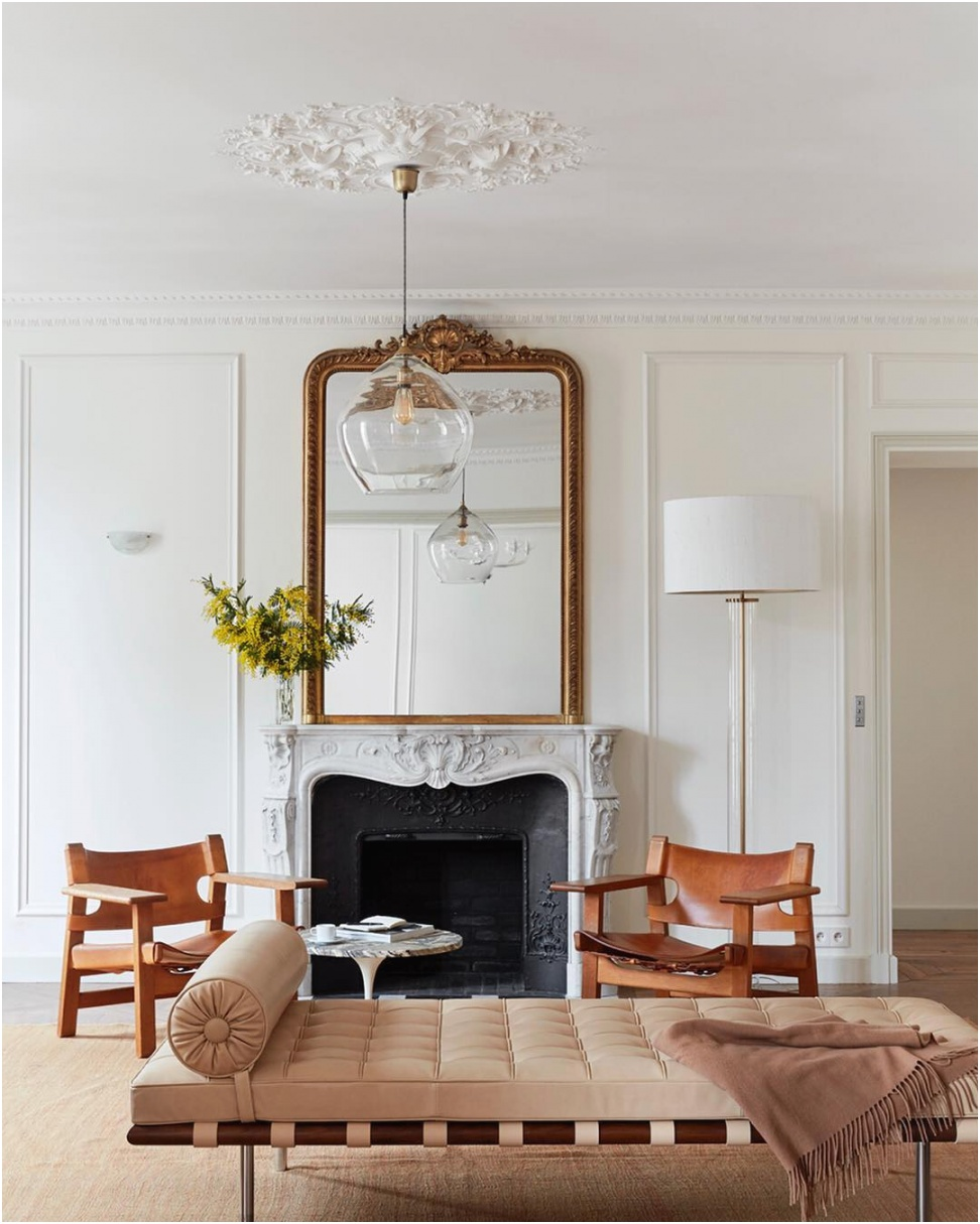 Parisian mirror in Paris apartment with fireplace and beige leather chairs via abkasha