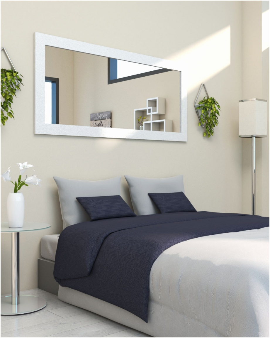 wide horizontal bedroom mirror in the wall behind bed