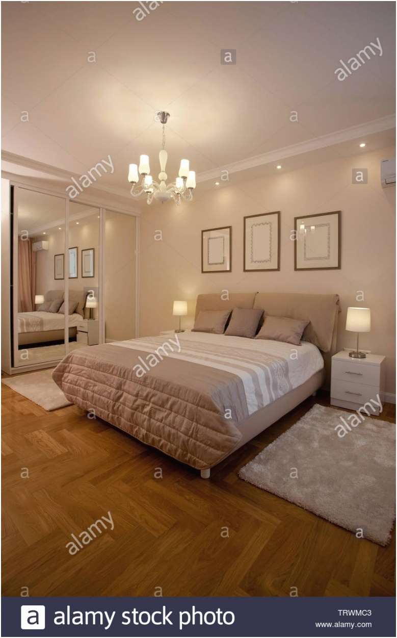 epmty minimalistic interior background bedroom of modern apartment with big mirrors double bed lights on nobody with copy space vertical TRWMC3