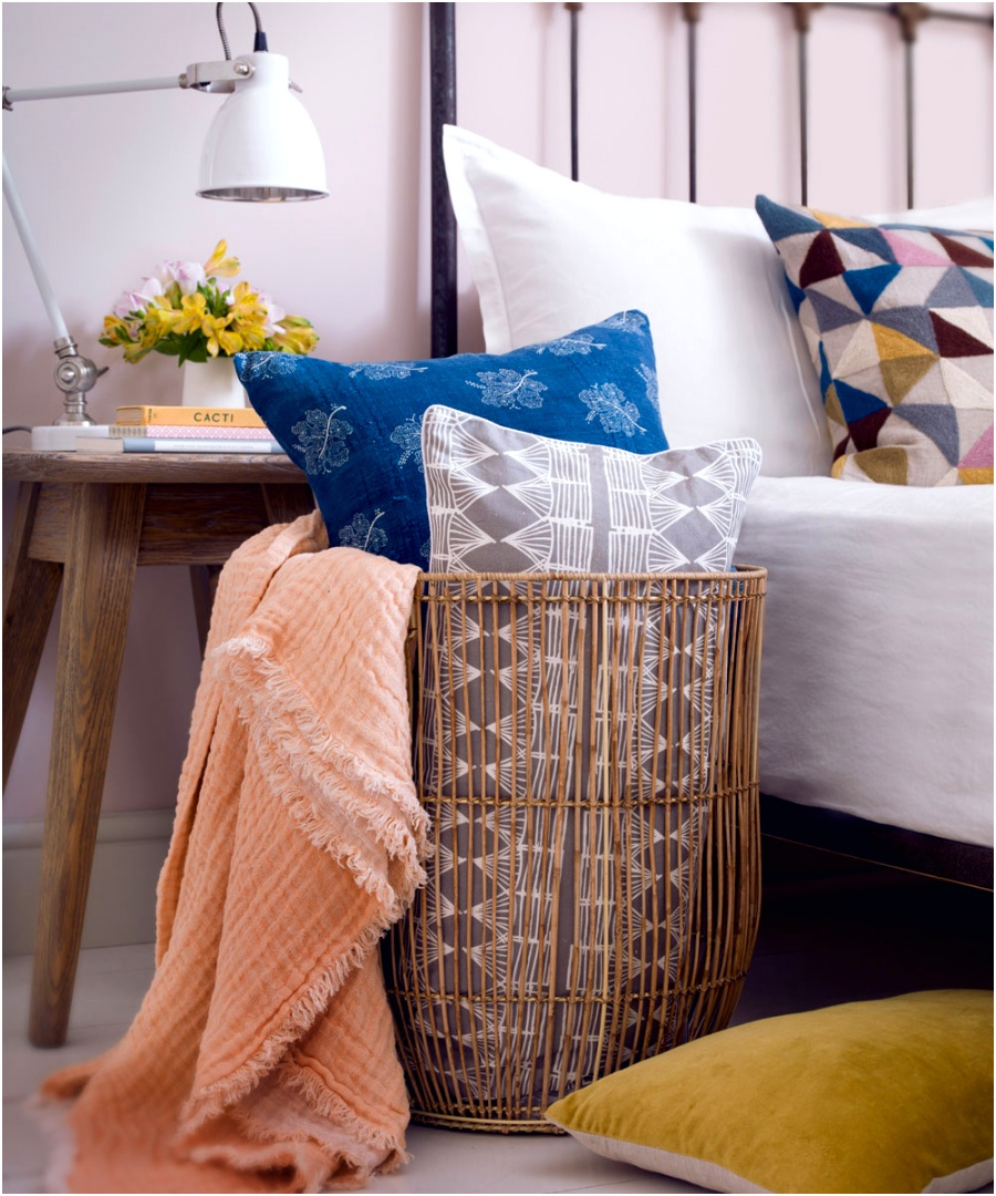 Country bedroom with woven basket and graphic cushions