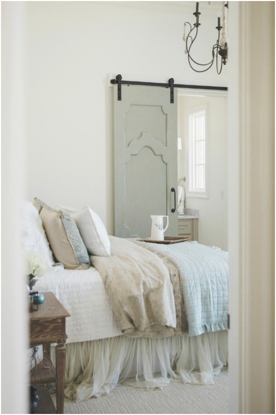 Rustic French farmhouse bedroom with light blue barn door
