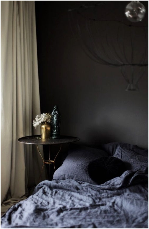 black walls graphite bedding and a refined nightstand with gold legs